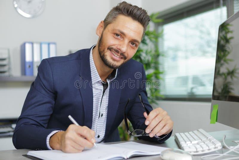 Retrato joven feliz del hombre de negocios en la oficina moderna brillante interior fotografía de archivo
