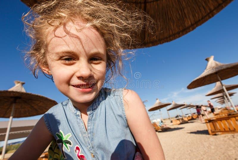 Retrato largo do ângulo da menina alegre da criança na praia do verão imagens de stock