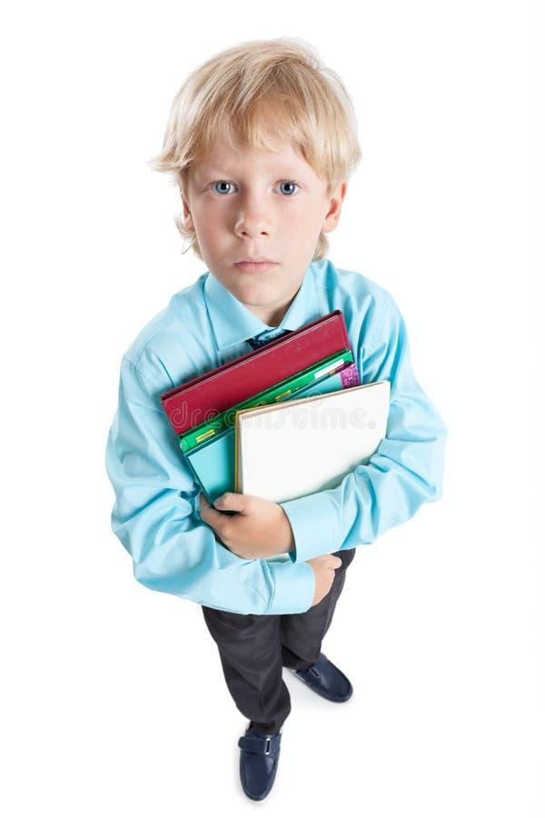 Retrato largo do ângulo do estudante do menino na camisa azul que abraça livros nas mãos, olhando a câmera, isolada no fundo bran fotos de stock royalty free