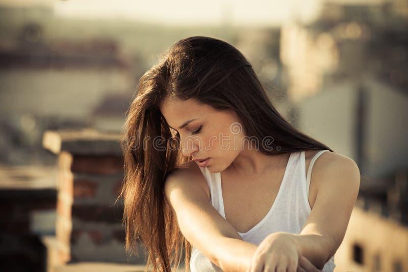 Retrato largo moreno del pelo de la muchacha de la ciudad en el tejado en la puesta del sol fotografía de archivo libre de regalías