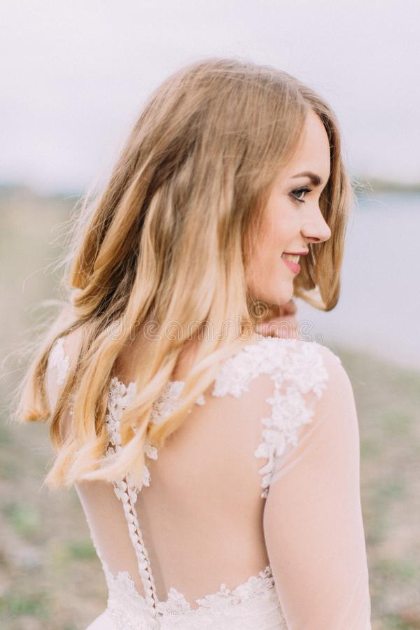 Retrato lateral al aire libre sensible de la novia sonriente en el fondo borroso de la playa fotografía de archivo libre de regalías