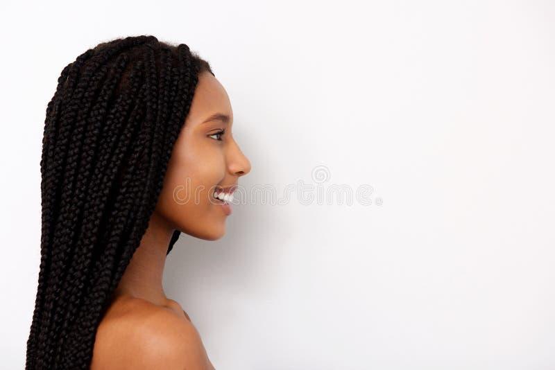 Retrato lateral da jovem mulher africana de sorriso com as tranças no fundo branco imagem de stock royalty free
