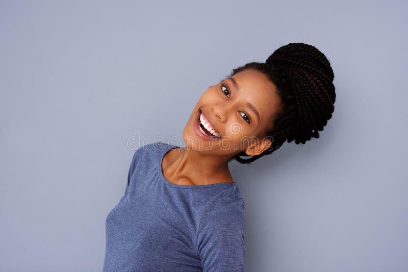 Retrato lateral da menina bonita com o bolo trançado do cabelo que ri no fundo cinzento fotos de stock royalty free