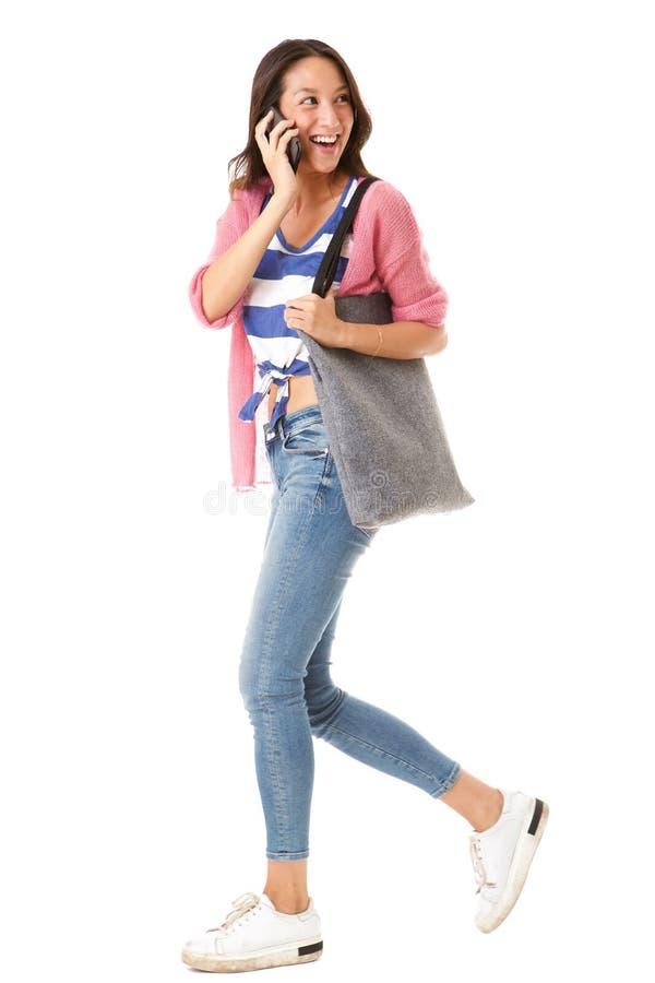 Retrato lateral da mulher asiática nova feliz que anda com bolsa e que fala no telefone celular contra o fundo branco isolado foto de stock