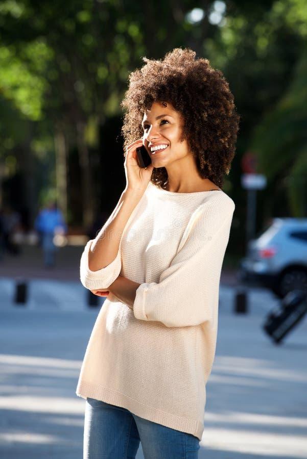 Retrato lateral da mulher de sorriso bonita que fala no telefone esperto imagem de stock
