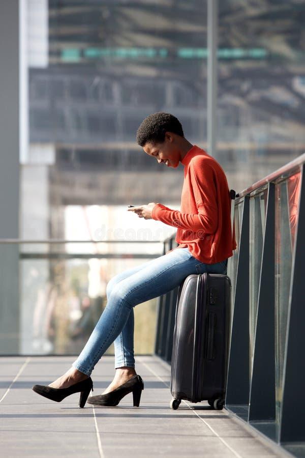 Retrato lateral da mulher nova de sorriso do curso que senta-se na mala de viagem na estação e que olha o telefone celular imagem de stock royalty free