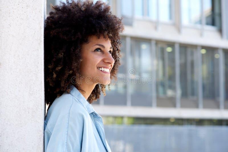 Retrato lateral da parte externa ereta de sorriso da mulher pela construção urbana foto de stock royalty free