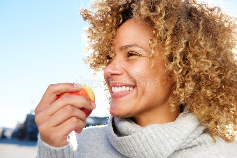 Retrato lateral de la manzana afroamericana joven sana de la tenencia de la mujer imagenes de archivo