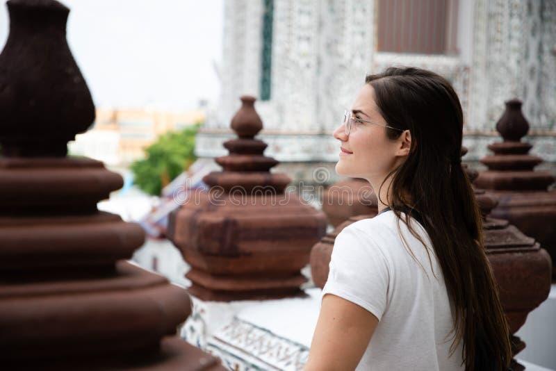 Retrato lateral de la mujer hermosa con el pelo largo marrón entre las columnas tailandesas de la decoración del templo foto de archivo libre de regalías
