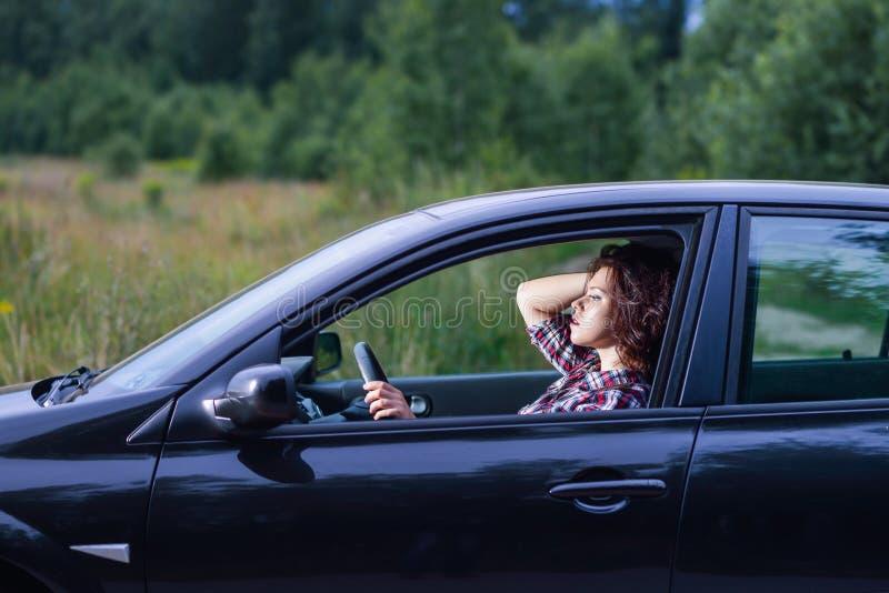 Retrato lateral de la mujer joven que conduce un coche foto de archivo libre de regalías