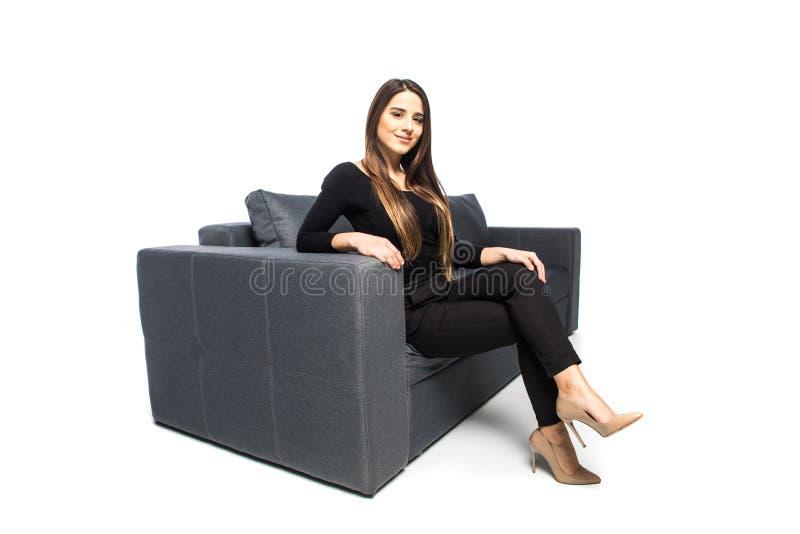Retrato lateral de la mujer sonriente que se sienta en el sofá en el fondo blanco Lanzamiento interior del estilo sport fotos de archivo