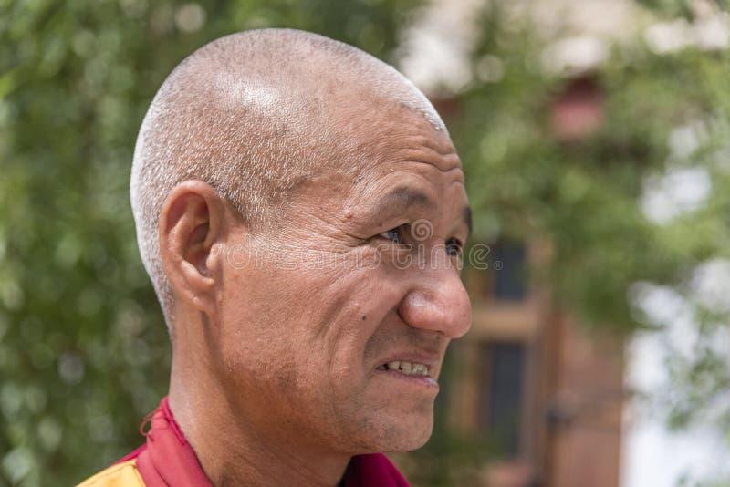 Retrato lateral de un viejo monje budista tibetano imagenes de archivo