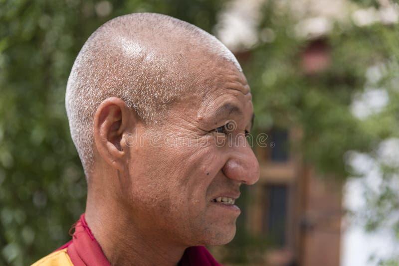 Retrato lateral de un viejo monje budista tibetano foto de archivo