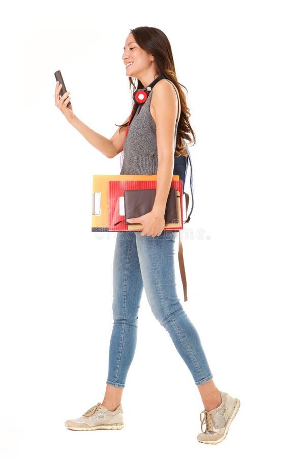 Retrato lateral del estudiante universitario asiático sonriente que camina contra fondo blanco aislado con el teléfono móvil foto de archivo