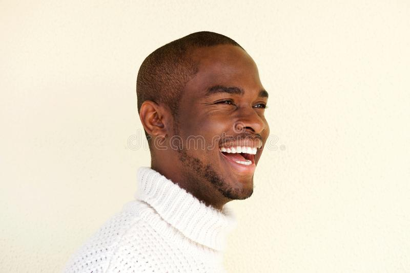 Retrato lateral del hombre afroamericano hermoso en suéter que ríe y que mira lejos foto de archivo libre de regalías