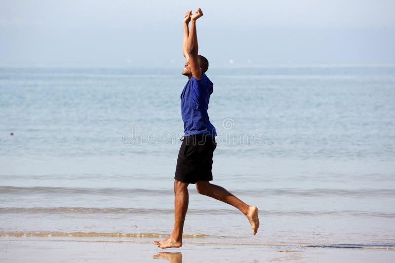 Retrato lateral del hombre negro extático que corre en orilla de mar con los brazos aumentados fotos de archivo