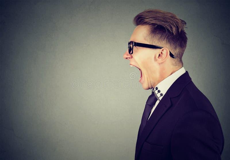Retrato lateral del perfil de un hombre de negocios joven enojado que grita fotografía de archivo libre de regalías