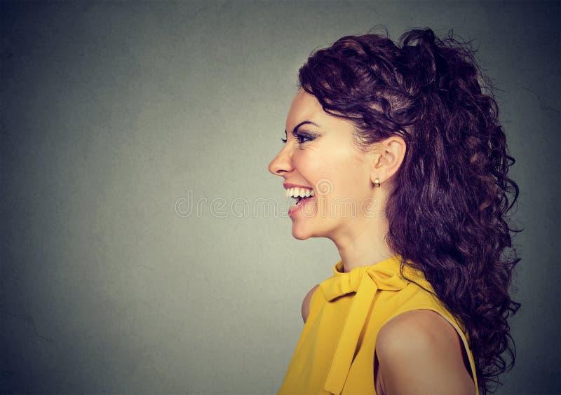 Retrato lateral del perfil de una mujer de risa feliz imágenes de archivo libres de regalías