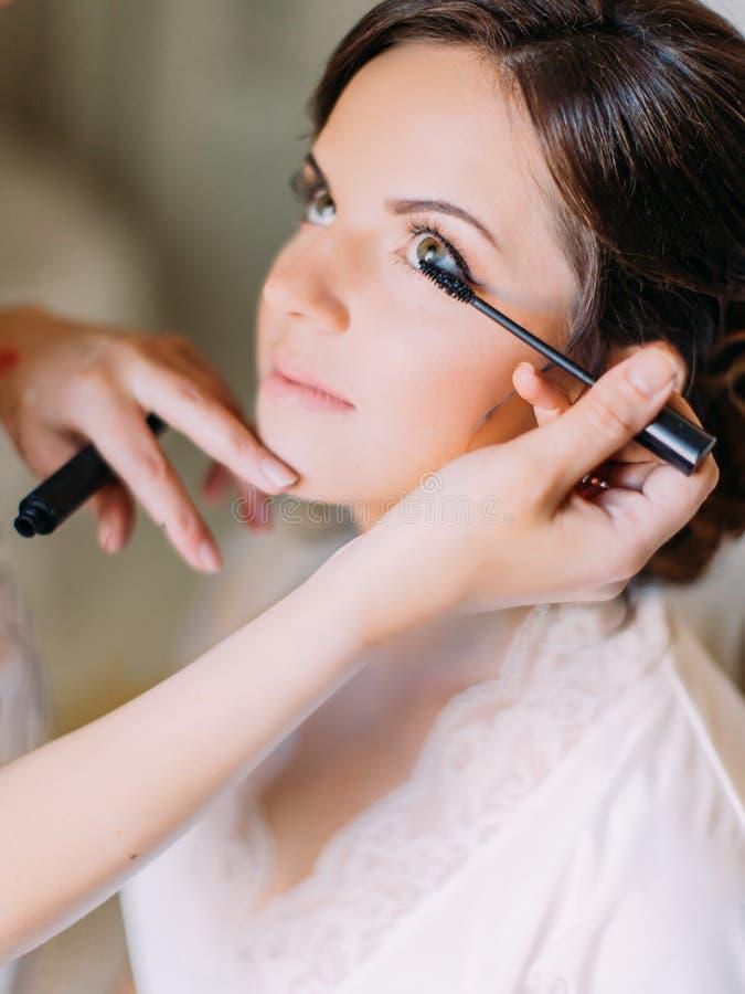Retrato lateral del primer del artista de maquillaje que hace el maquillaje para la novia feliz fotografía de archivo libre de regalías