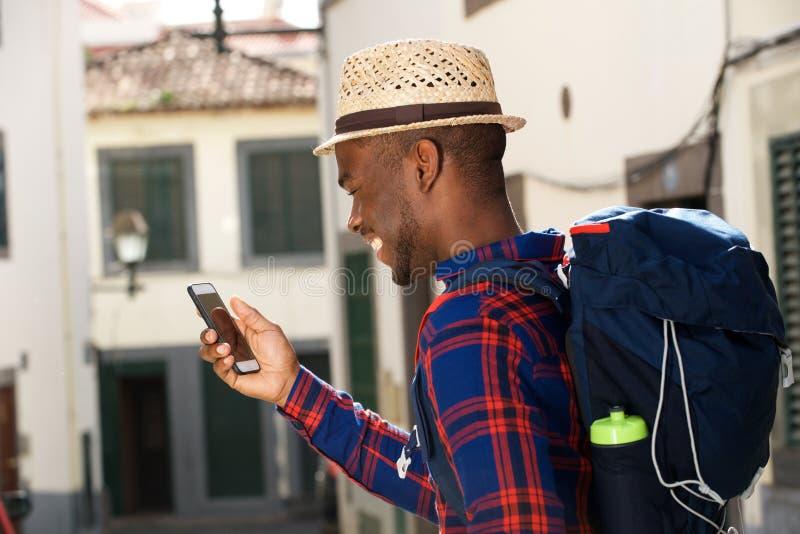 Retrato lateral do homem afro-americano feliz com trouxa e telefone celular imagens de stock