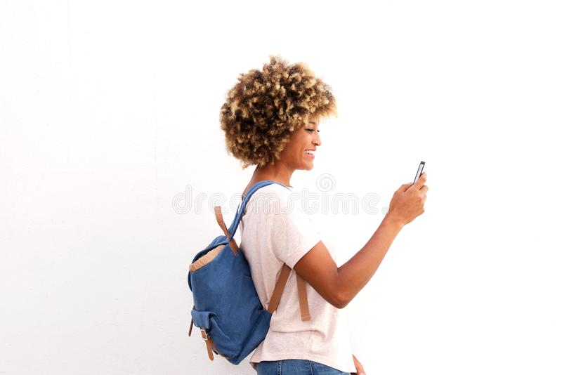 Retrato lateral do telefone esperto de vista fêmea afro-americano contra o fundo branco foto de stock