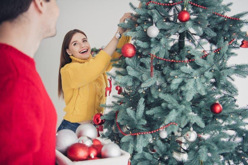 Retrato lateral trasero de dos personas alegre mujer decoran los baubles de la mano de abeto verde gozar de preparación para x foto de archivo libre de regalías