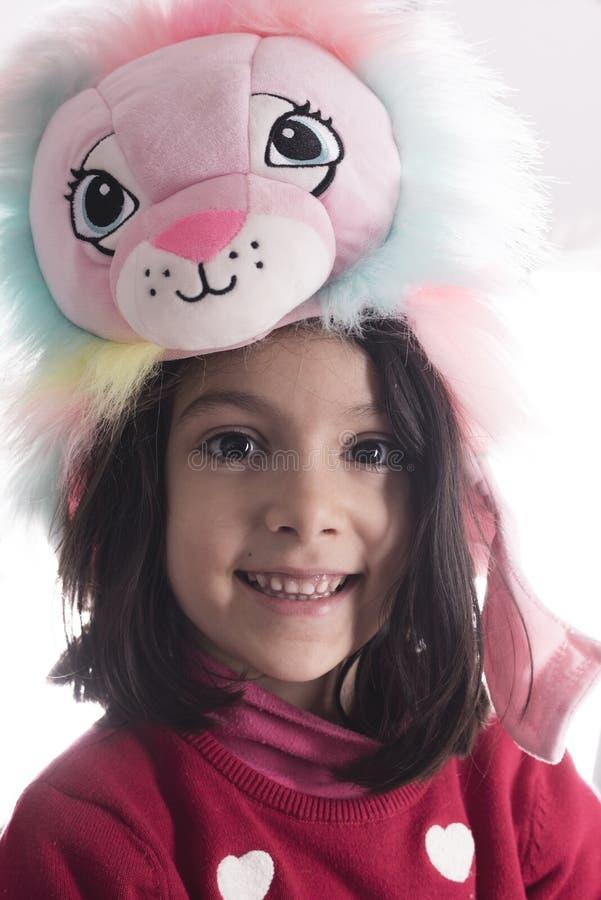Retrato lindo de la muchacha con el sombrero del muppet del león que mira la cámara foto de archivo libre de regalías
