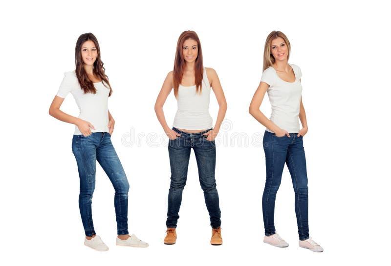 Retrato lleno de tres muchachas casuales con vaqueros y las camisetas blancas imágenes de archivo libres de regalías