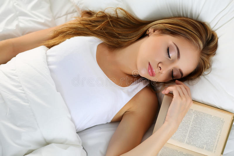 Retrato louro bonito novo da mulher que encontra-se na cama que dorme em b imagens de stock royalty free