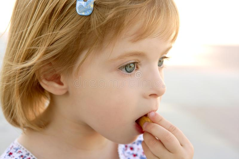 Retrato louro do close up da menina que come o biscoito fotos de stock royalty free