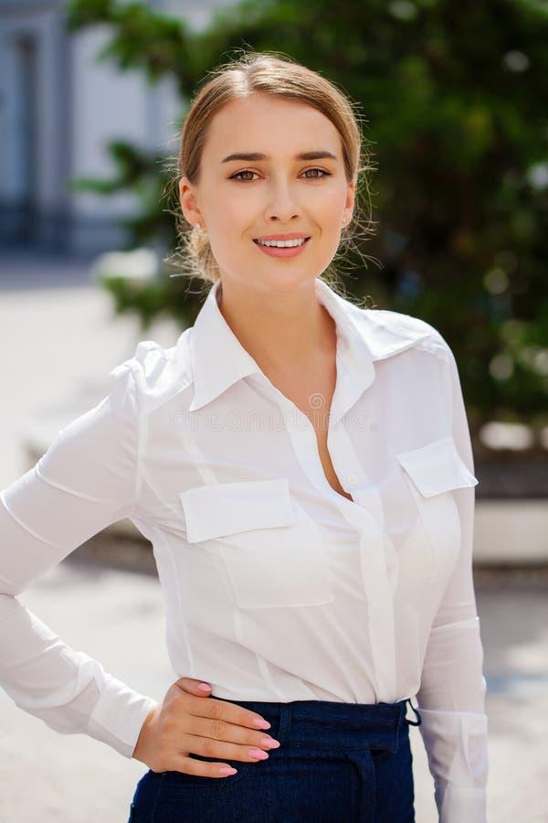 Retrato, louro novo do negócio na camisa branca na rua do verão imagem de stock