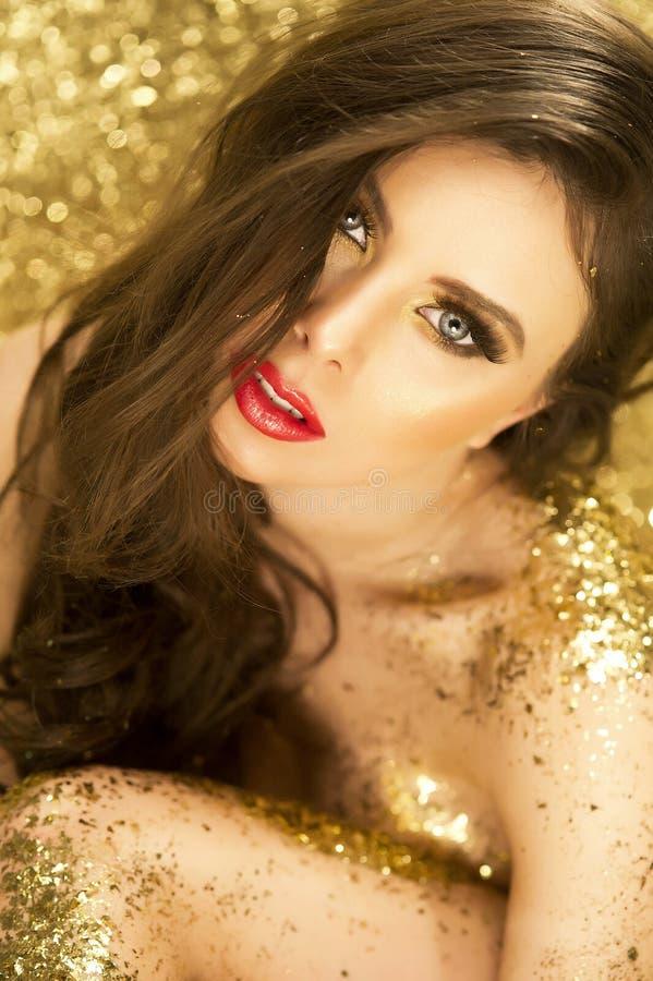 Retrato 'sexy' da menina no ouro fotografia de stock royalty free