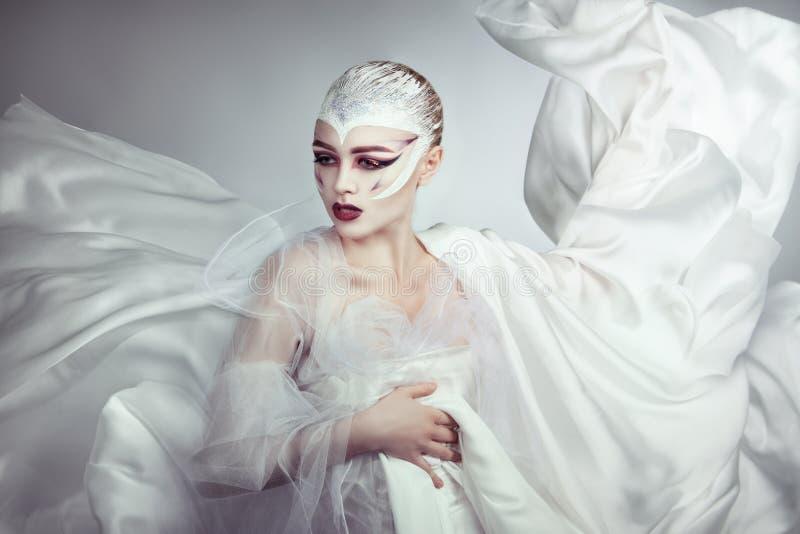 Retrato mágico de una mujer hermosa con maquillaje brillante La muchacha en un vestido blanco que fluye imagen de archivo