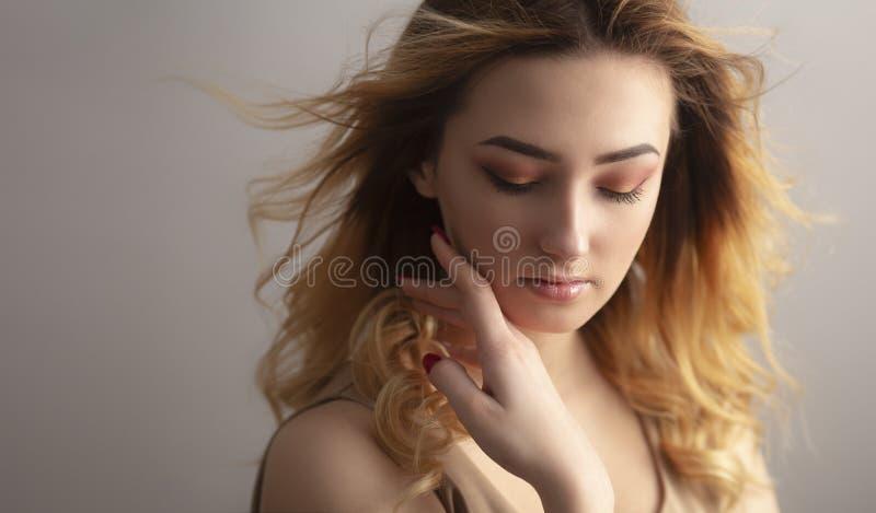 Retrato macio de uma jovem mulher bonita, cara com o cabelo encaracolado emaranhado do vento, o conceito do estúdio da menina da  foto de stock royalty free