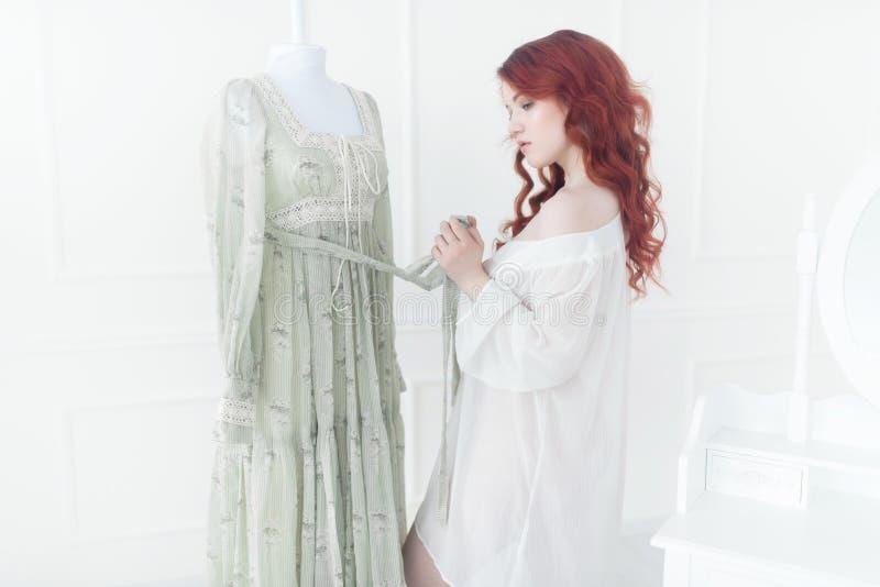 Retrato macio de uma mulher sonhadora nova do ruivo na camiseta Está estando na sala do vestido e está planejando vestir o vintag foto de stock royalty free