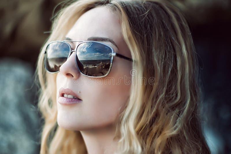 Retrato macro de óculos de sol vestindo da cara da mulher com reflexão imagem de stock