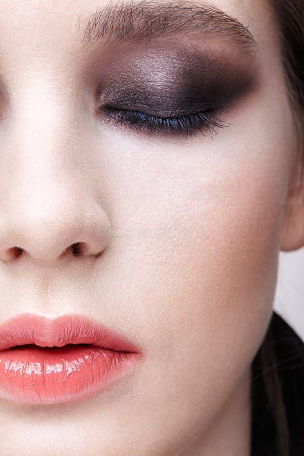 Retrato macro del primer de la cara femenina Muchacha con la piel y la violeta perfectas - maquillaje ahumado negro de los ojos imagen de archivo libre de regalías