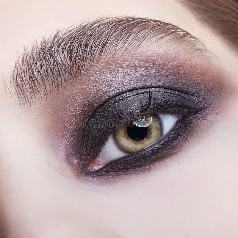Retrato macro del primer del ojo femenino humano con violeta - maquillaje ahumado negro de los ojos foto de archivo