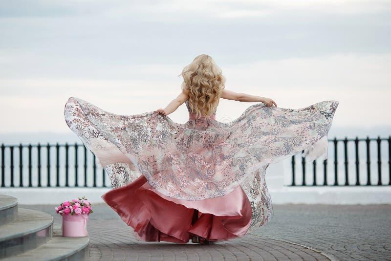 Retrato magnífico de una muchacha rubia en un vestido rosado atractivo de la tarde con un ramo de rosas hermosas fotos de archivo libres de regalías