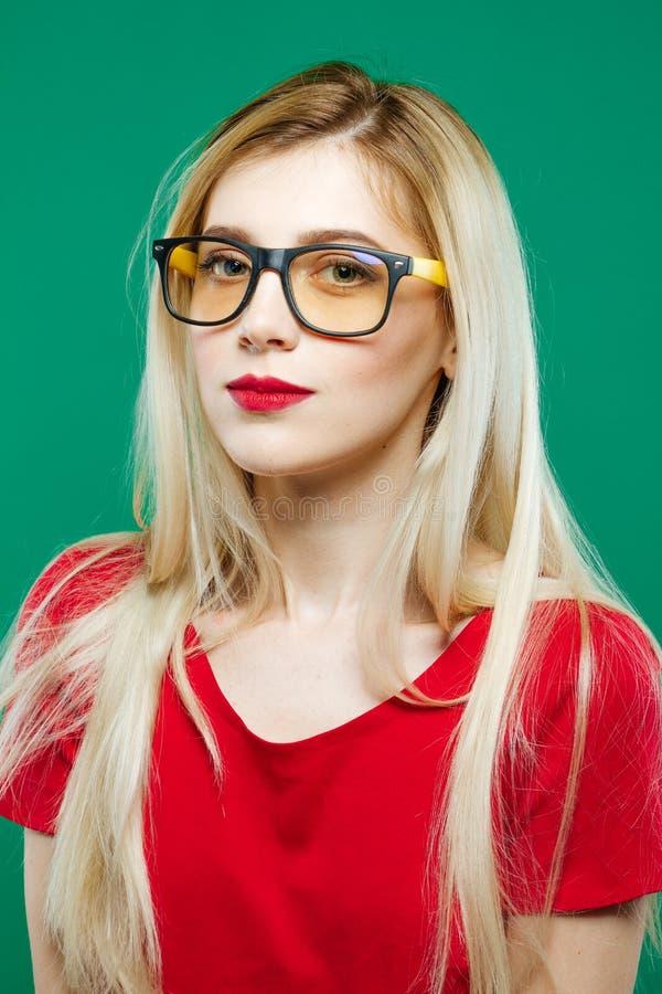 Retrato maravilloso de la muchacha elegante linda en lentes y top rojo Cortocircuito del estudio del Blonde hermoso en fondo verd imagen de archivo libre de regalías