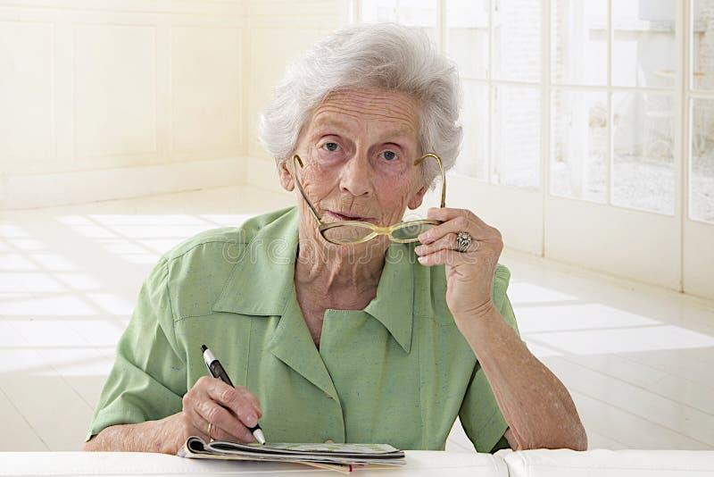 Retrato mayor de la mujer que sostiene los vidrios y que hace el crucigrama fotos de archivo