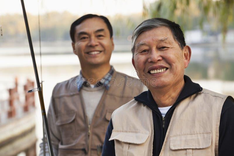 Retrato mayor de los amigos mientras que pesca en un lago imagenes de archivo