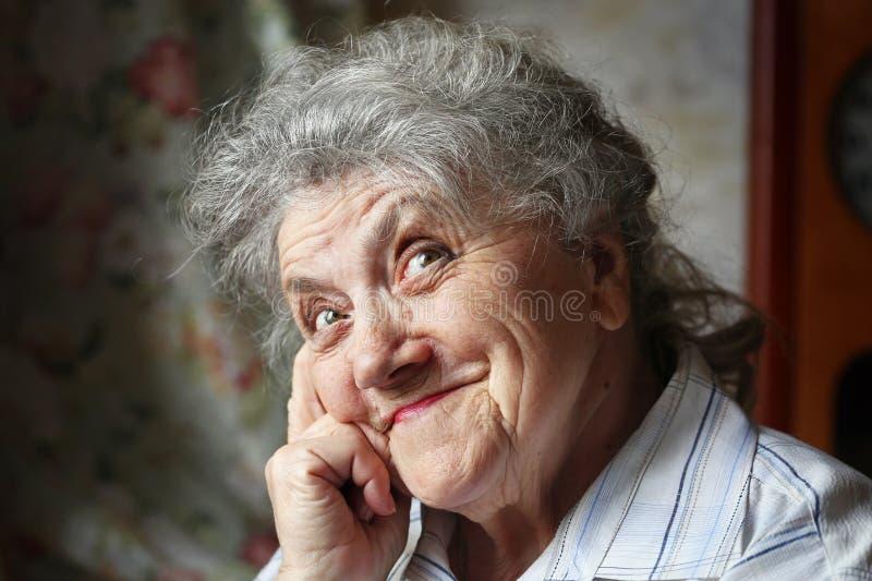 Retrato mayor feliz de la mujer en un fondo oscuro imagen de archivo