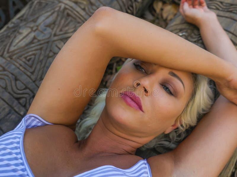 Retrato melancólico del aire libre de la mentira rubia atractiva y hermosa joven de la mujer relajada en tronco en el bosque o el imagen de archivo libre de regalías