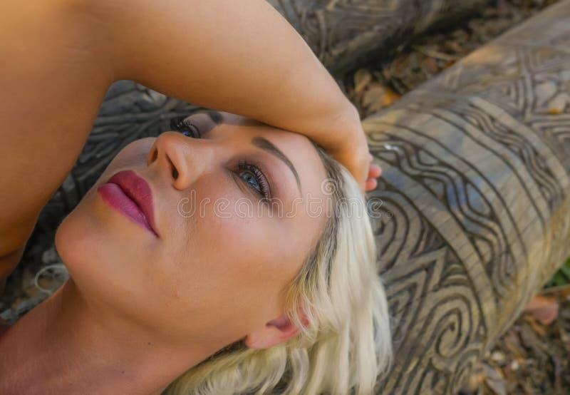Retrato melancólico do ar livre do encontro louro atrativo e bonito novo da mulher relaxado no tronco na floresta ou no parque do fotografia de stock royalty free