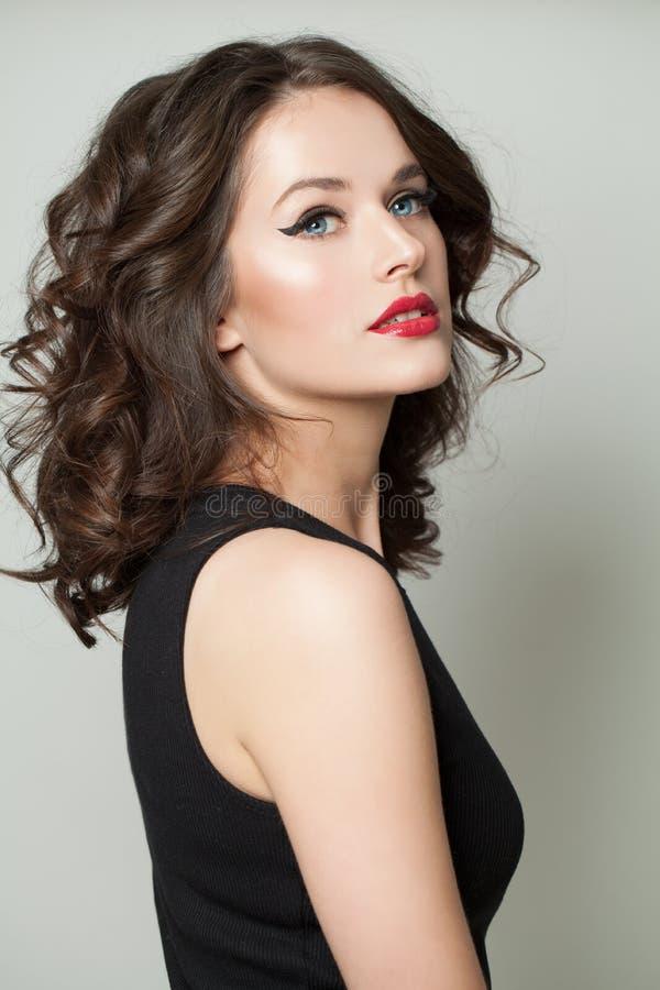 Retrato modelo agradable de la muchacha Mujer atractiva con maquillaje y el retrato rizado marrón del peinado fotografía de archivo