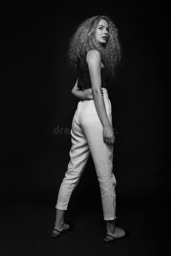 Retrato monocromático completo da jovem mulher que levanta sobre o fundo preto Tiro do estúdio da forma fotos de stock royalty free