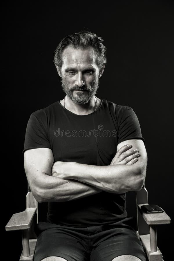 Retrato monocromático del hombre del stong que se sienta en silla en estudio imagenes de archivo