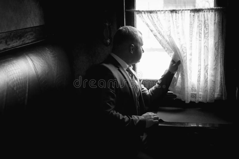 Retrato monocromático do homem que senta-se no cupê do trem e que olha a OU fotos de stock royalty free