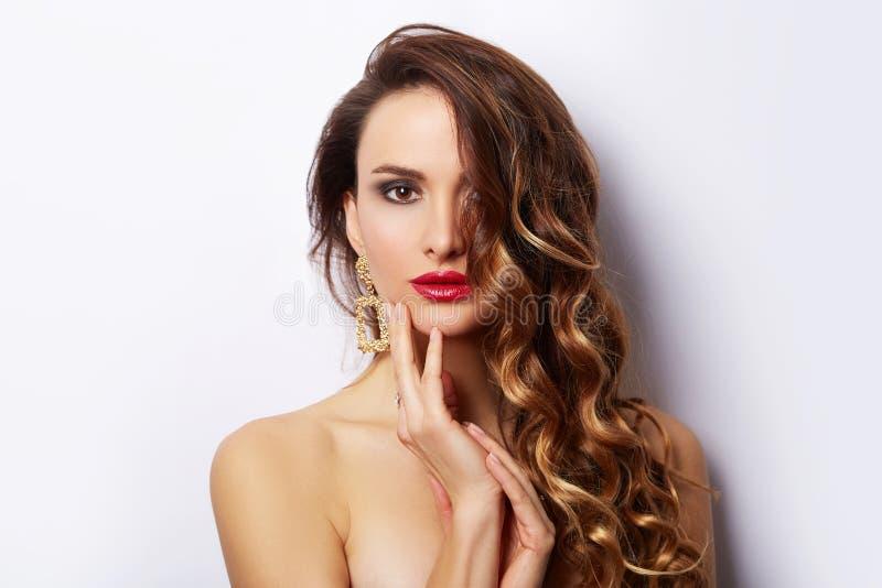 Retrato moreno de la muchacha de la moda de la belleza con el pelo rizado Mujer atractiva del encanto que iguala los pendientes d fotos de archivo libres de regalías